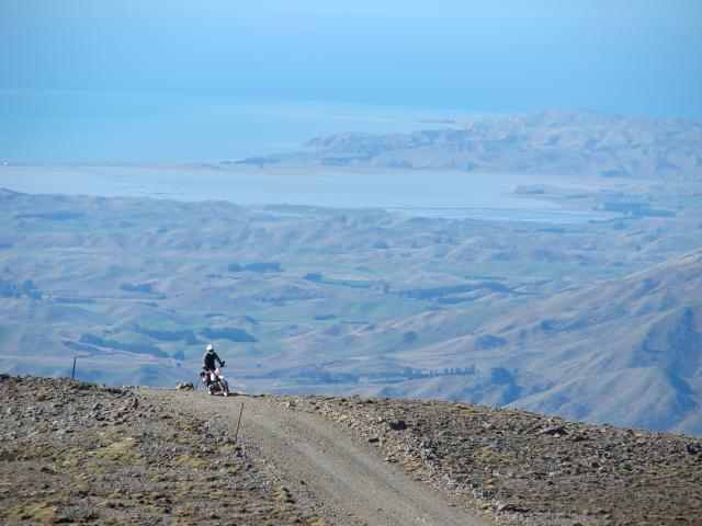 A rider crests a hill on Mt Altimarloch with amazing views in the background