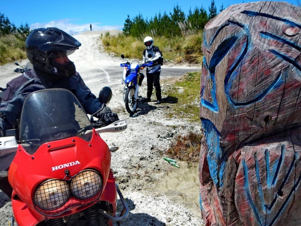 Kel, on his Africa Twin, eyes up the totem