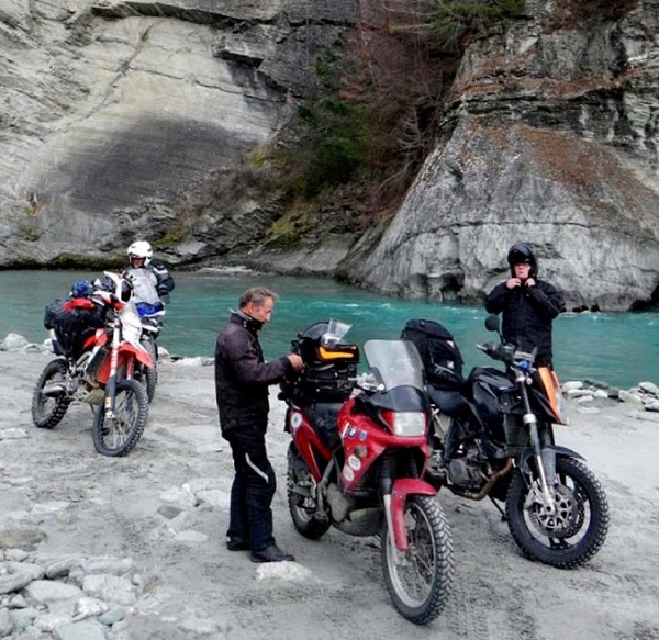 Riders rest beside the river in Skippers Canyon