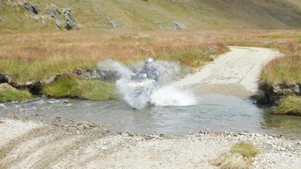 A KLR rider gest enthusiatic on a river crossing.